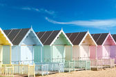 Traditional British beach huts on a bright sunny day — Stok fotoğraf