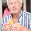 Senior man eating fish — Stock Photo