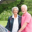 Senior couple with black car — Stock Photo