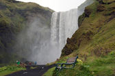 Iceland - Southern Iceland - bench in front of waterfall Skogafoss — Stock Photo
