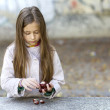 Autumn girl with chestnuts - Stock Photo