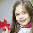 Girl holding read autumn leaf - Stock Photo