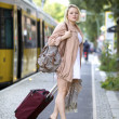Young woman pulling luggage - Stock Photo