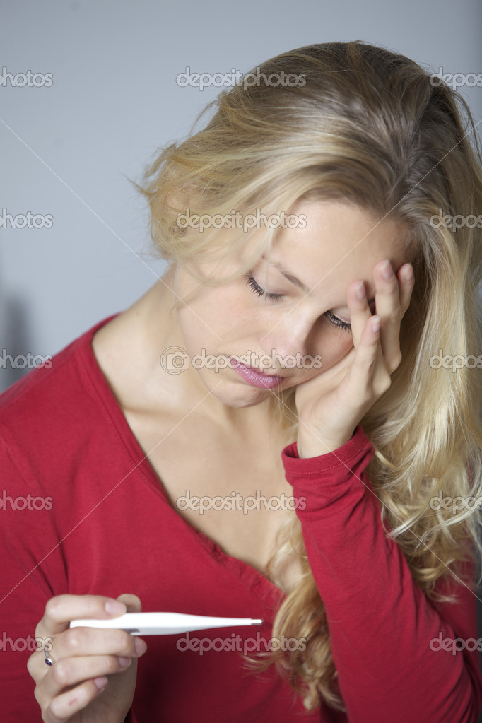 Young woman not feeling well holding a thermometer and checking her temperature.  Stock Photo #14726147