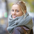 Royalty-Free Stock Photo: Smiling young woman in scarf enjoying winter