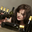 Drunk woman with bottles. - Stock Photo