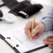 Filling out a patient information form - Stock Photo