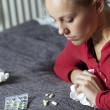 Sick young woman with medicine - Stock Photo