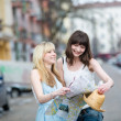 Two women sightseeing and looking at the map - Stock Photo