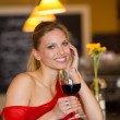 Cheerful young woman in a bar with red wine - Stock Photo