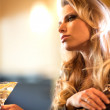 Pensive young woman with cocktail - Foto Stock