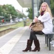 Stock Video: Sitting young womwaiting for public transportation