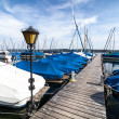 Covered boats and yachts docked at wooden pier — Stock Photo
