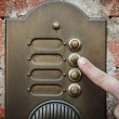 Finger ringing a door bell - Stock Photo