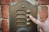 Finger ringing a door bell — Стоковое фото