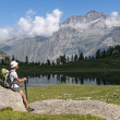 Resting and admiring panoramduring trekking in Alps — Stock Photo #30302215