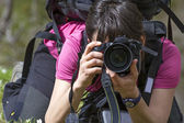 Young woman photographer in action — Stock Photo