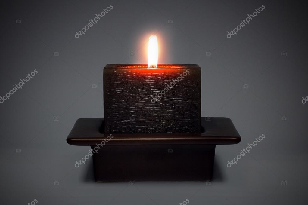 Square candle with a candlestick on a gray background.  Stock Photo #19038097