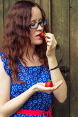 Red-haired girl holding a strawberry. — Stock Photo