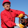 Smiling Oil Worker Turning Valve On Oil Rig - Stock Photo