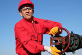 Smiling Oil Worker Turning Valve On Oil Rig — Stock Photo