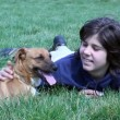 Stock Video: Boy Laying In Grass With His Dog