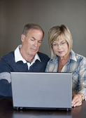 Mature couple using laptop — Stock Photo