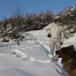Stock Video: MPlaying With her Dog with snow on winter landscape