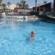 Stock Video: Mswimming in swimming pool on vacation