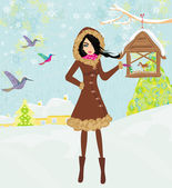 Girl feeds the birds in winter — Stock Vector