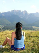 Girl resting on the grass in the mountain area  — Stock Photo