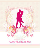 Floral greeting card with silhouette of romantic kissing couple  — Stockvector