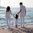 Happy young family with daughter on beach in summer — Stockfoto