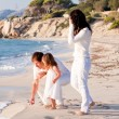 Stock Photo: Happy young family with daughter on beach in summer