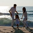 Happy young family with daughter on beach in summer — Stock Photo #13194735