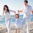 Happy young family with daughter on beach in summer — Stock Photo