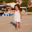 Little cute girl smiling playing on beach in summer — Stock Photo