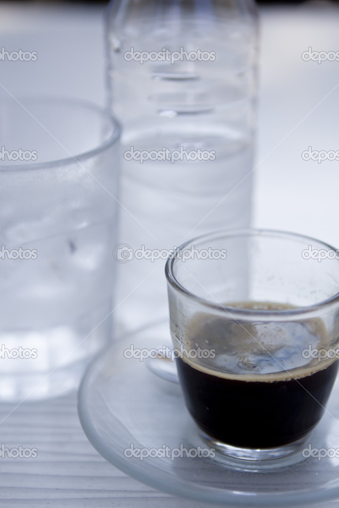 Hot aromatic espresso cup and cold water in glass in a cafe in summer outdoor — Stock Photo #13193730