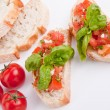 Deliscious fresh bruschetta appetizer with tomatoes isolated - Stock Photo