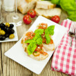 Fresh tasty italian bruschetta with tomato on table — 图库照片