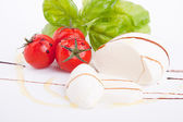 Tasty tomatoe mozzarella salad with basil on white — Stock Photo