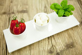 Tasty tomatoes mazarella and basil on plate on table — Stock Photo