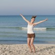 Cheerful woman jumping laughing at beach portrait — Stock Photo #13556933