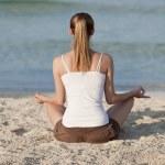 Woman doing yoga on the beach Sports Landscape — Stock Photo #13557076