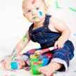 Cute little baby painting and splatter with colours — Stock Photo