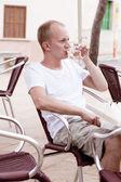 νεαρός άνδρας κάθεται εξωτερική σε ένα καφέ το καλοκαίρι — Φωτογραφία Αρχείου