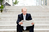 Young business man is reading newspaper outdoor — Stock Photo