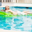 Young man is swimming with air mattress in pool — Stock Photo #15633557