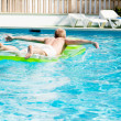 Young man is swimming with air mattress in pool — Stock Photo #15633567