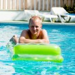 Young man is swimming with air mattress in pool — Stock Photo